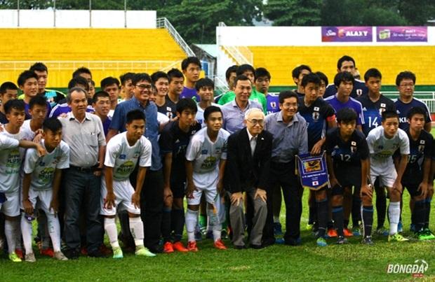 Bầu Đức không ngại mưa xuống sân chụp hình cùng các cầu thủ nhí của 2 đội. Ảnh: Quang Thịnh